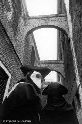 Ref VENICE 12 – Two carnival figures passing under old arches
